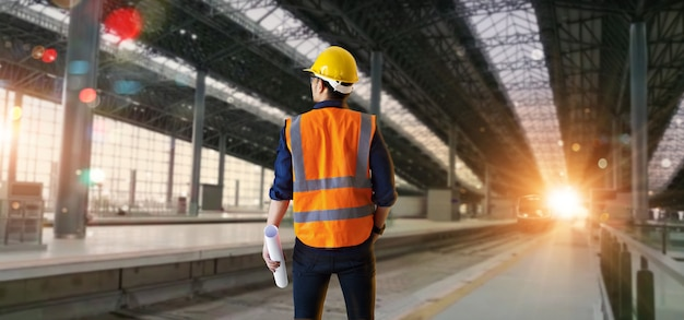 Manager industrieel ingenieur die blauwdrukken vasthoudt en structuur en bouwspoorweg controleert