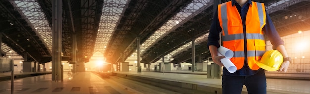 Manager industrieel ingenieur met een blauwdruk op de bouwplaats van de spoorweg van technology