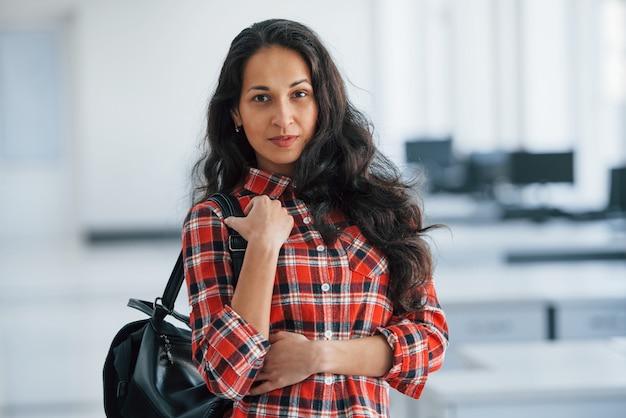 Manager is aangekomen op kantoor. portret van aantrekkelijke jonge vrouw met zwarte tas