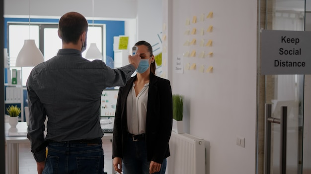 Manager met beschermend gezichtsmasker onderzoekt de temperatuur van collega's met een infraroodthermometer voordat hij op kantoor komt tijdens de pandemie van het coronavirus. collega's die sociale afstand houden om covid te voorkomen19