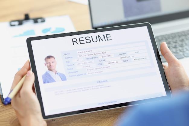 Manager onderzoekt de elektronische vragenlijst van de sollicitant bij het zoeken naar een baan op de tablet en het schrijven van cv's