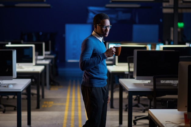 Manager poseert met kopje koffie, office lifestyle. mannelijke persoon aan tafel, donker zakencentrum interieur, moderne werkplek