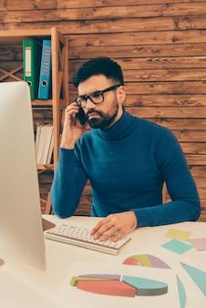 Manager praten over de telefoon met zijn klanten en werken met pc