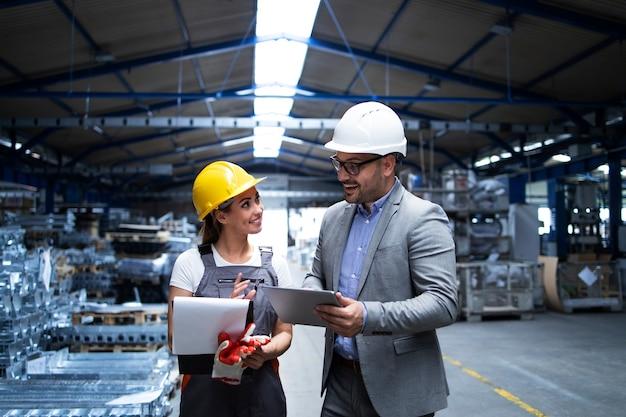 Manager supervisor en werknemer bespreken over productieresultaten en nieuwe strategie in industriële fabriekshal