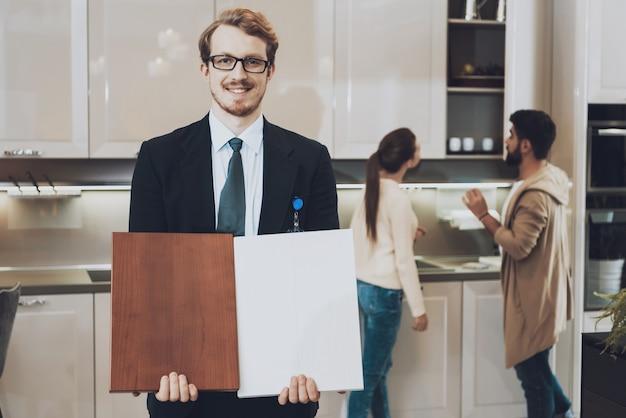 Manager toont kastmaterialen in de keukenwinkel