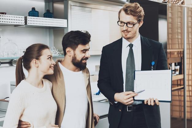 Manager toont keukenblauwdrukken om klanten in de keukenwinkel te koppelen.