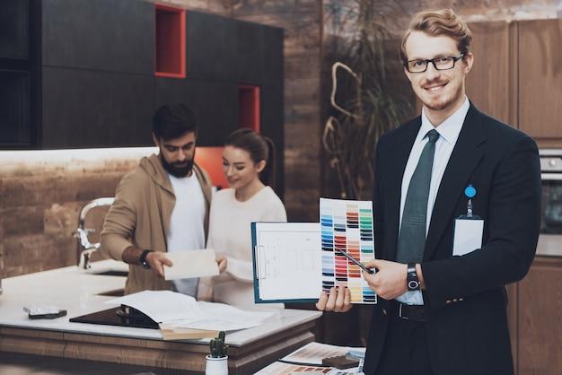 Manager toont kleurstalen en blauwdrukken met een paar klanten op de achtergrond in de keukenwinkel.