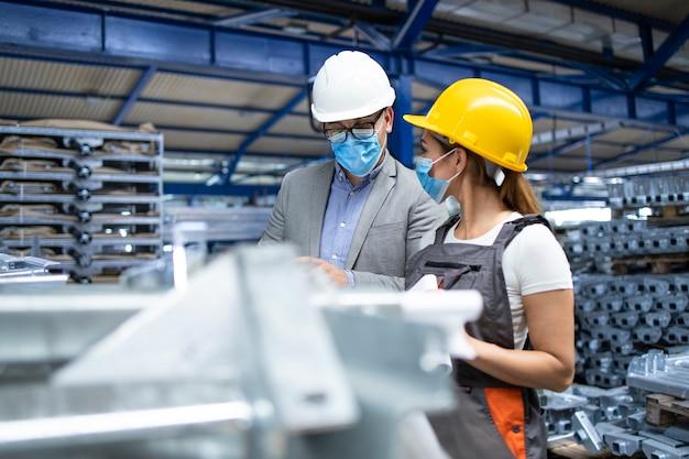 Manager van de industriële supervisor met hygiënisch masker in gesprek met werknemer in productiefabriek
