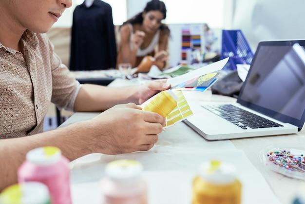 Manager van naaiatelier die het palet van kleurstalen controleert en online nieuwe vormen van garens bestelt