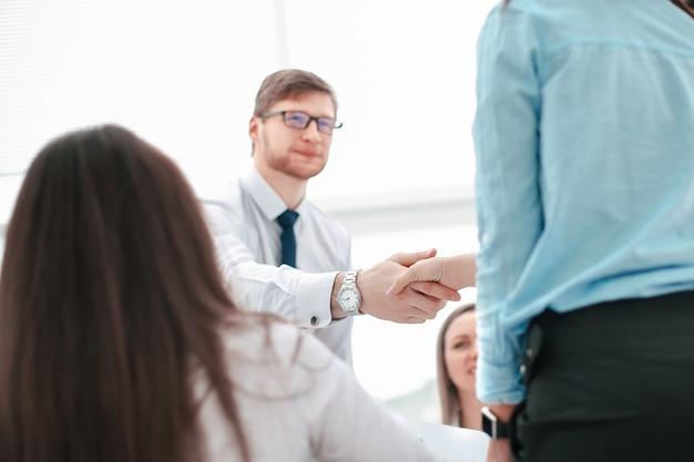 Manager verwelkomt de projectmanager voor de vergadering.