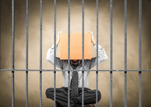 Manager zit achter de tralies van een gevangenis met zijn hoofd in een doos