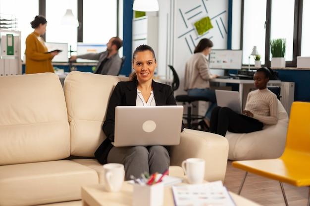 Managerdame die op laptop schrijft en naar de camera kijkt terwijl ze glimlacht terwijl diverse collega's op de achtergrond werken
