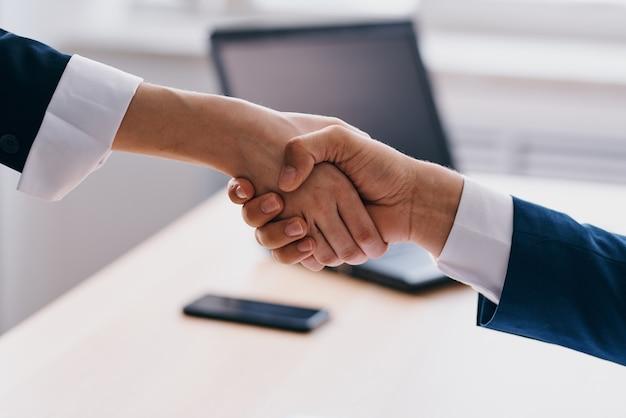 Managers handen schudden succesvolle deal kantoorlaptopprofessionals