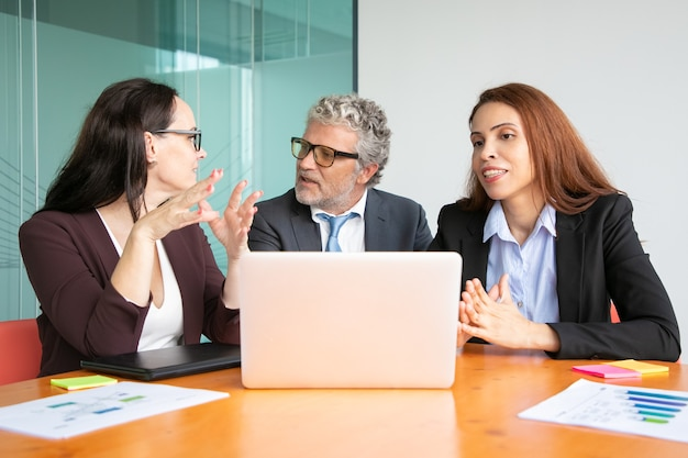 Managers ontmoeten elkaar aan tafel met opengeklapte laptop, bespreken en delen ideeën met baas.