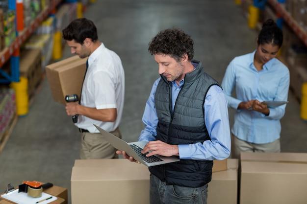 Managers staan en werken in het midden van kartonnen dozen