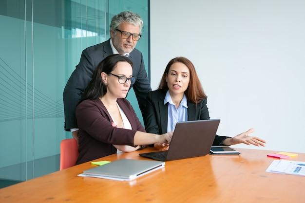 Managers tonen presentatie op laptop aan stafmedewerker, wijzend op display, details uit te leggen.