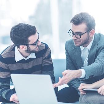 Managers van het bedrijf en de klant, bespreken de voorwaarden van het nieuwe contract en kijken naar het laptopscherm met de juiste informatie.
