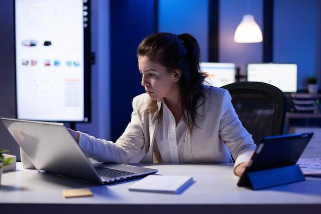 Managervrouw die laptop en tablet gebruikt die tegelijkertijd aan financiële rapporten werkt