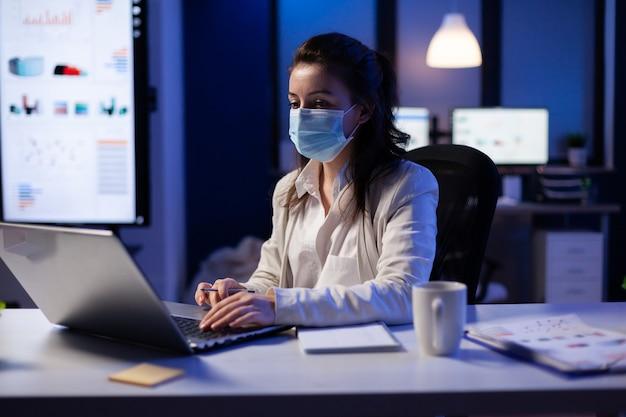 Managervrouw met gezichtsmasker die overwerkt in nieuw normaal bedrijfsbureau die teamproject op professionele laptop bekijken