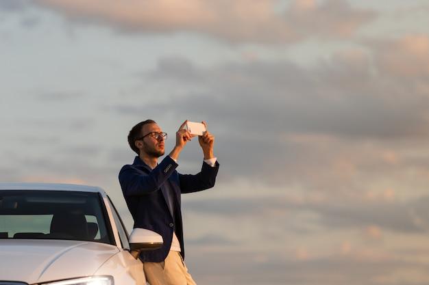Manchauffeur stopte om een foto van de zonsondergang te maken met een mobiele smartphone