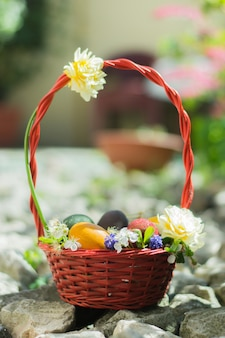 Mand gevuld met kleurrijke paaseieren en versierd met witte bloemen op de rotsen