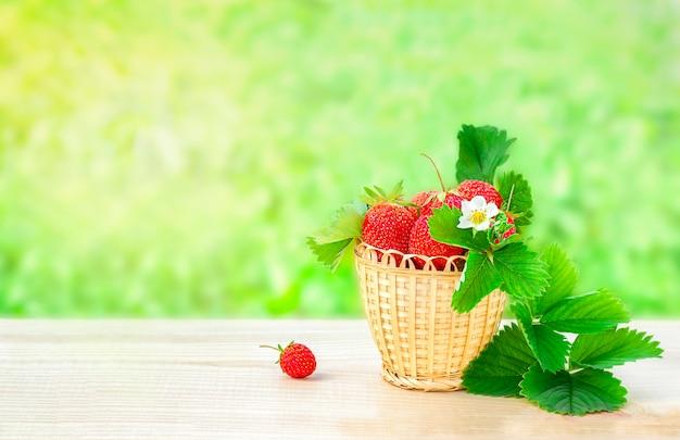 Mand met aardbeien staat buiten op een houten tafel