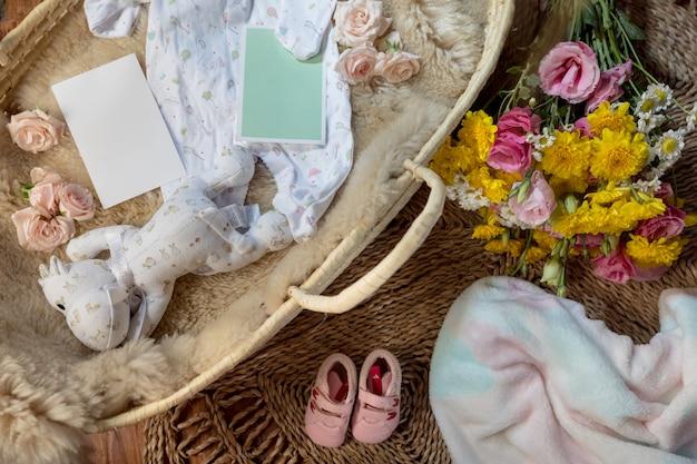 Mand met bloemen, babykleertjes, dekens, knuffel en poster