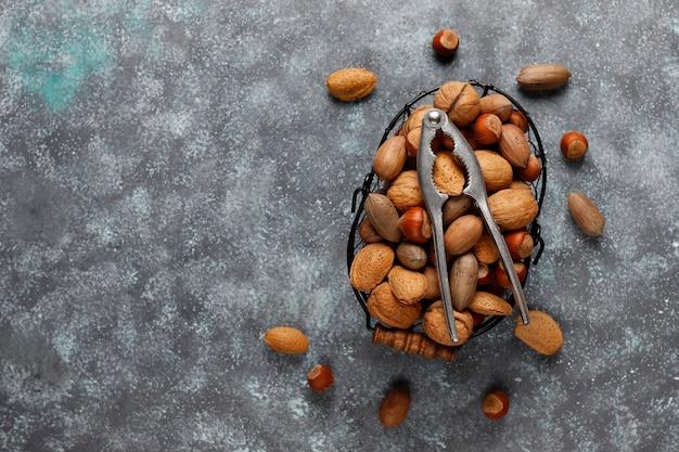 Mand met diverse noten en notenkraker over marmer