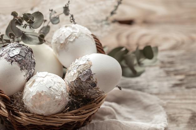 Mand met eieren en gedroogde bloemen op een onscherpe achtergrond. een origineel idee om paaseieren te versieren.