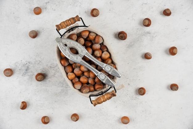 Mand met gepelde hazelnoten en notenkraker op marmeren tafel.