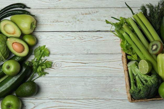 Mand met groene groenten op witte houten achtergrond