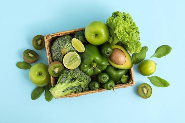 Mand met groente en fruit op blauwe achtergrond
