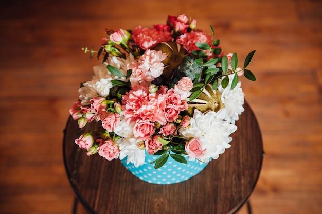 Mand met lentebloemen op een houten stoel