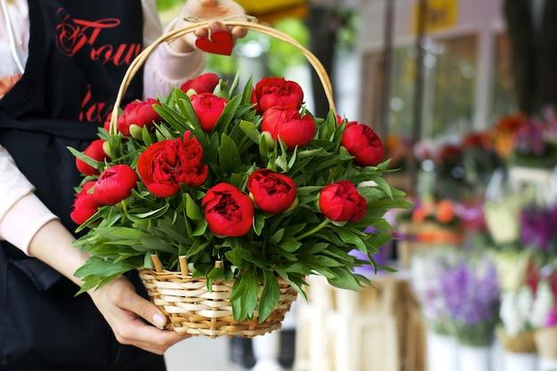 Mand met pioenrozen in handen van de verkoper van een bloemenboetiek
