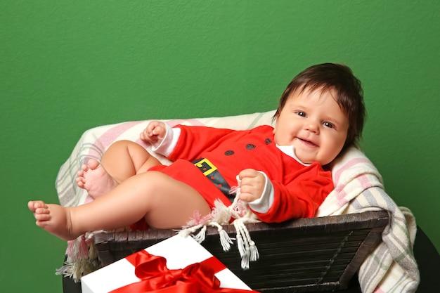 Mand met schattige baby in kerstmankostuum tegen kleurenmuur