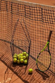 Mand met tennisballen en racket tegen net op gravel
