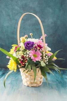 Mand met verschillende bloemen die op bureau worden geplaatst