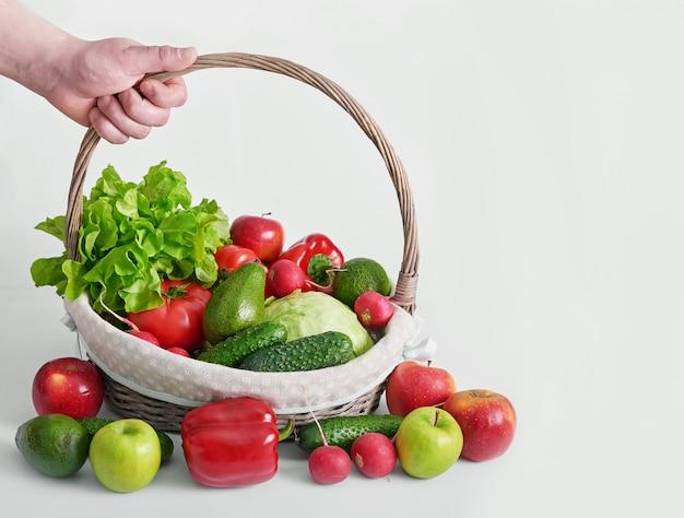 Mand met verschillende geïsoleerde groenten.