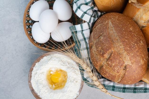 Mand met verschillende soorten brood samen met bloem en eieren. hoge kwaliteit foto
