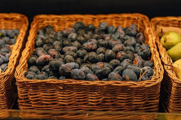 Mand met verse blauwe pruimen in supermarkt afbeelding met selectieve focus