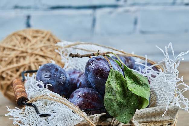 Mand met verse pruimen op houten tafel, close-up.