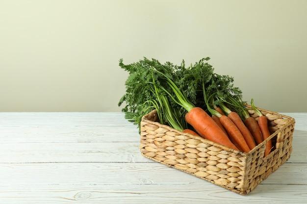 Mand met wortel op witte houten tafel