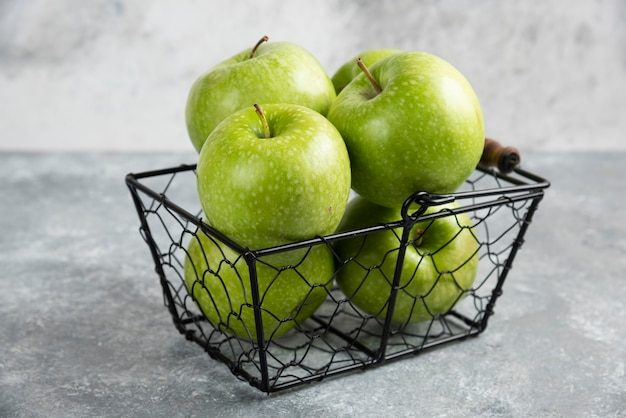 Mand vol groene glanzende appels op marmeren tafel.