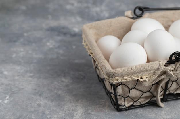 Mand vol verse witte kippeneieren op een marmeren achtergrond.
