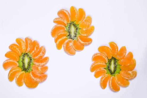 Mandarijn- en kiwiplakken bestaande uit drie decoratieve vormen in de vorm van bloemen op een witte uitknipachtergrond