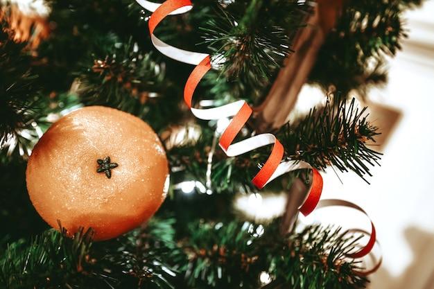 Mandarijn en serpentijn op de kerstboom nieuwjaarssamenstelling kerstboomtakken