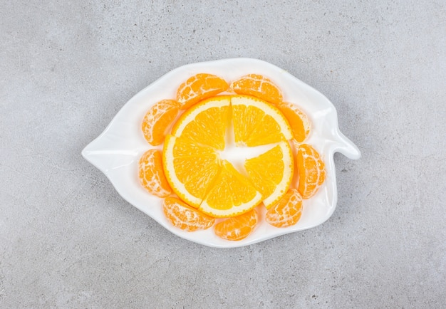 Mandarijn en stukjes sinaasappel op een witte plaat.