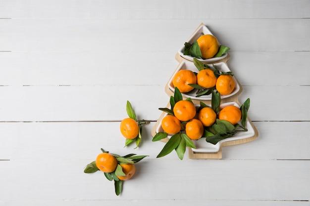Mandarijn in de vorm van een kerstboom op houten achtergrond. kerst breacfast idee voor kinderen.