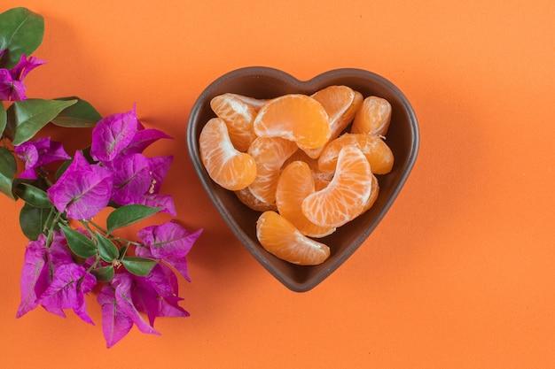 Mandarijn in hartplaat dichtbij de purpere bloem op oranje oppervlakte