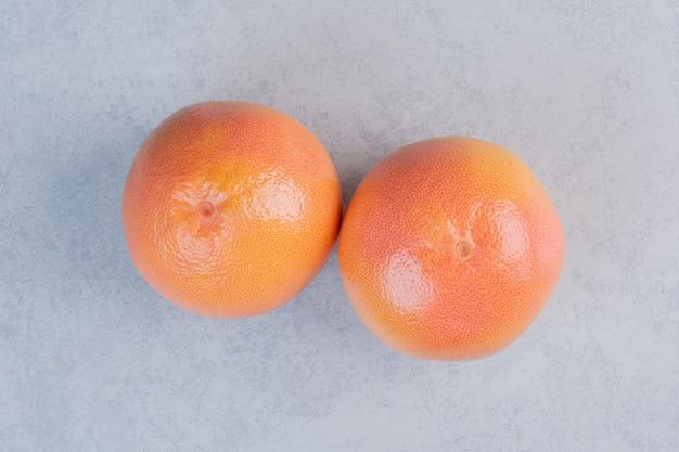 Mandarijn of clementine geïsoleerd op een grijze achtergrond.